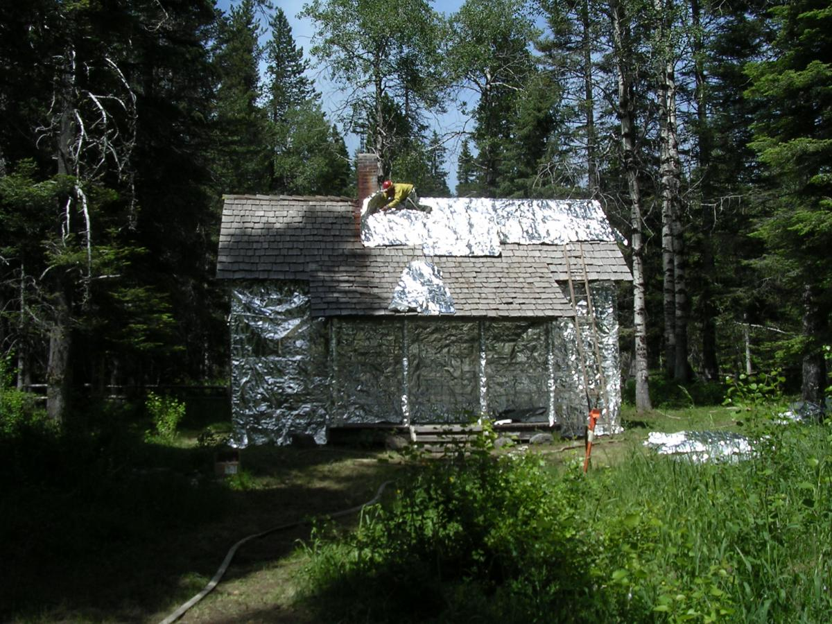 Gotchen Creek Ranger Station being wrapped for protection against forest fire.